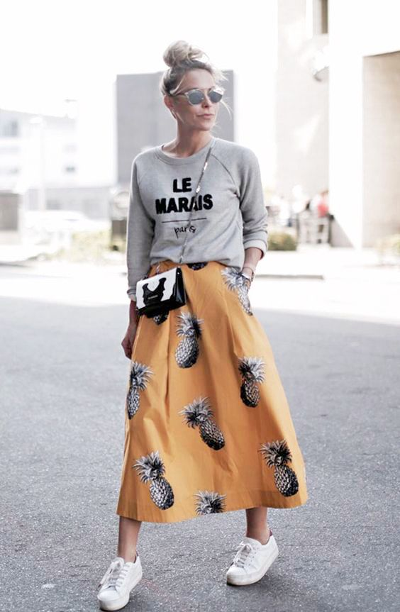 a grey printed sweatshirt, white sneakers and a bold yellow pineapple print midi skirt as a statement