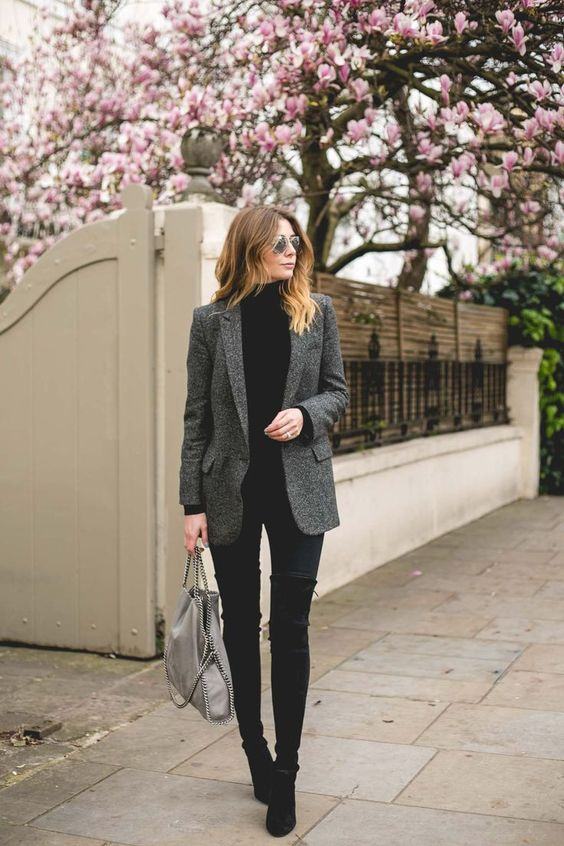 black jeans, a black turtleneck, tall boots and a grey blazer for a stylish look