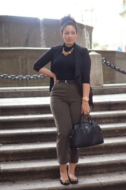 olive green cropped pants, a black turtleneck, a black cardigan, a statement necklace and black flats