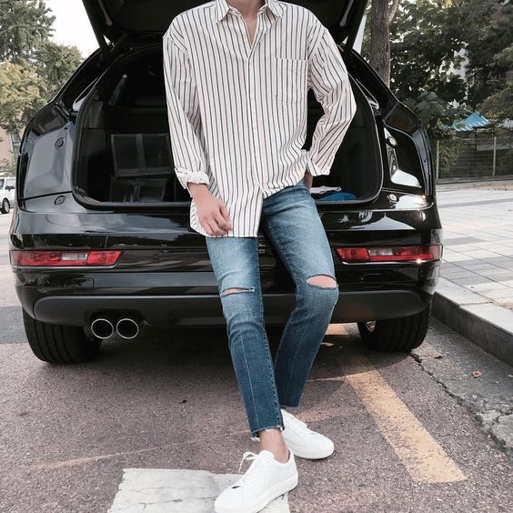 white Vans sneakers, distressed jeans, a loose striped shirt for a weekend look