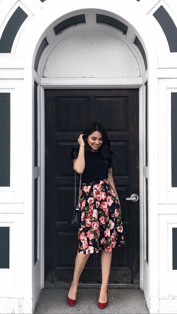 a black top with a knee floral skirt is a timeless solution with a girlish touch