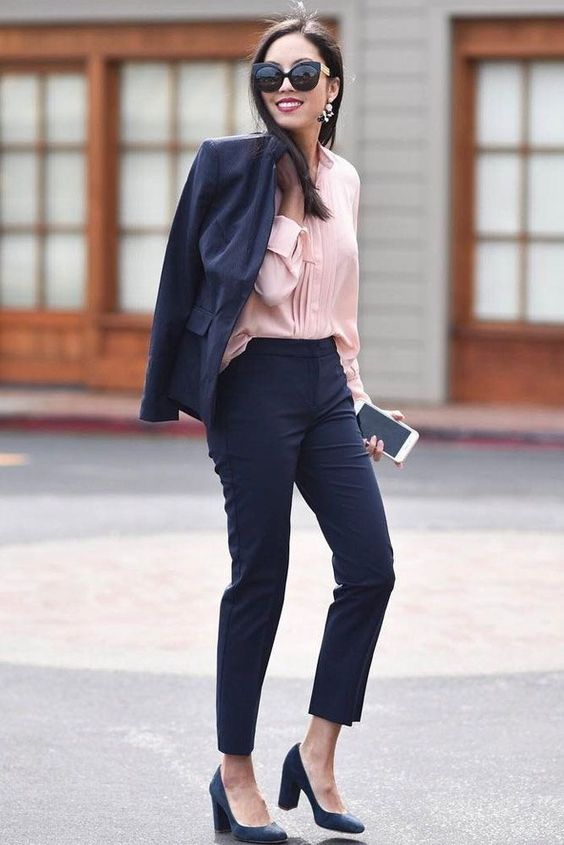 a navy pantsuit with cropped pants, a pink shirt and blue shoes for a professional look