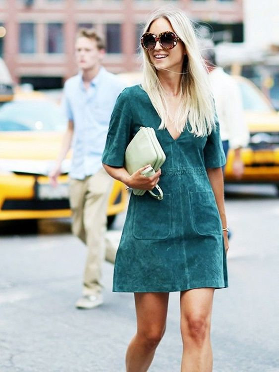 an emerald suede mini dress with a deep V-neckline and a light green clutch