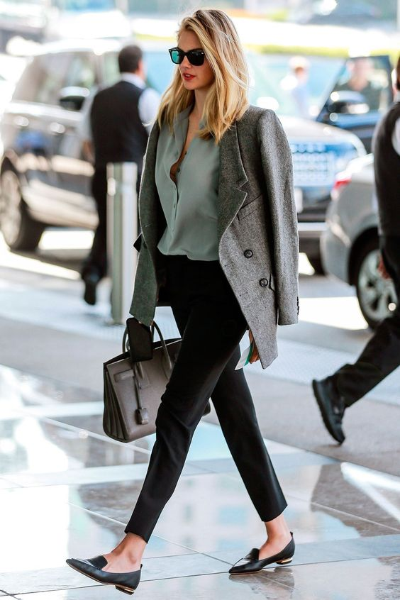 black pants, a muted green shirt, black flats, a grey short coat