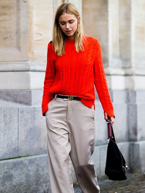 neutral wide pants, a red cable knit sweater and a comfy bag