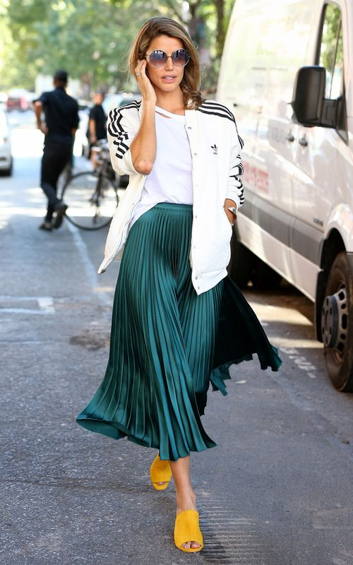 yellow mules, a white top, a green pleated midi and a sport hoodie for an eclectic look