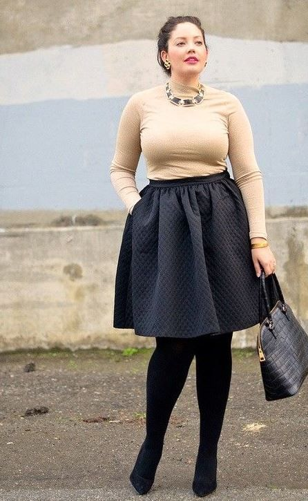 a black knee skirt, black tights, black shoes, a neutral top with long sleeves and a statement necklace