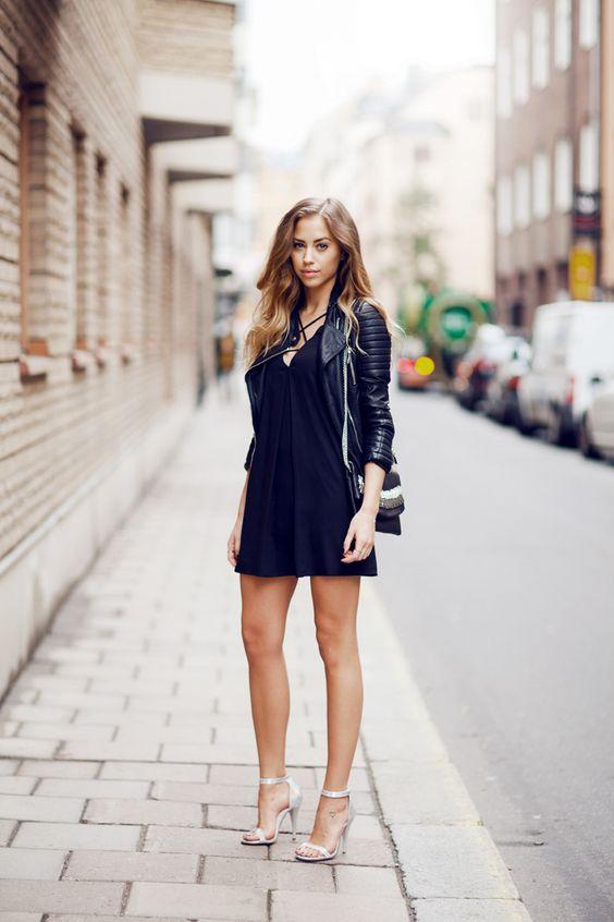 a black mini dress, a black leather jacket, metallic shoes and a striped bag