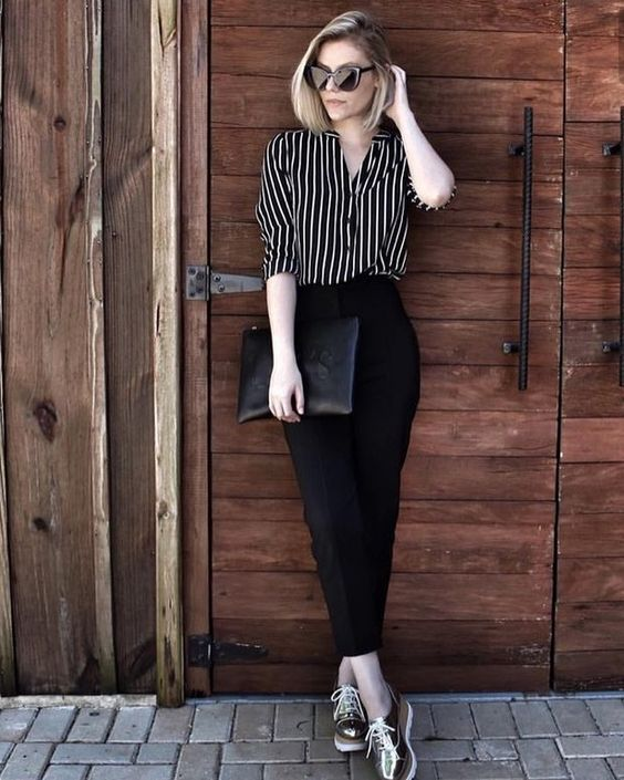 black pants, a striped black and white shirt, metallic platform shoes and a black clutch