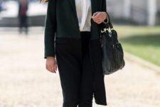 11 black pants, a white shirt, black boots and a color block coat in green and black