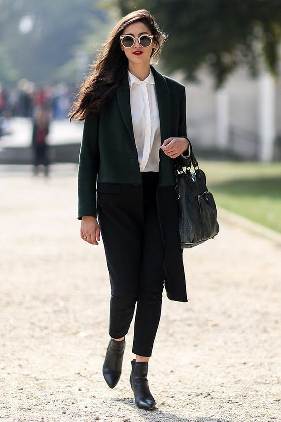 black pants, a white shirt, black boots and a color block coat in green and black