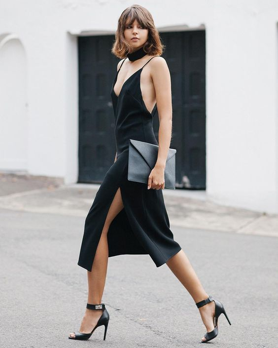 a black slip dress with a plunging neckline and a side slit, high heels and a chocker