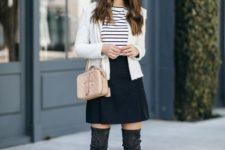 12 a black sude mini, a printed tee, a white jacket, tall black boots and a cap