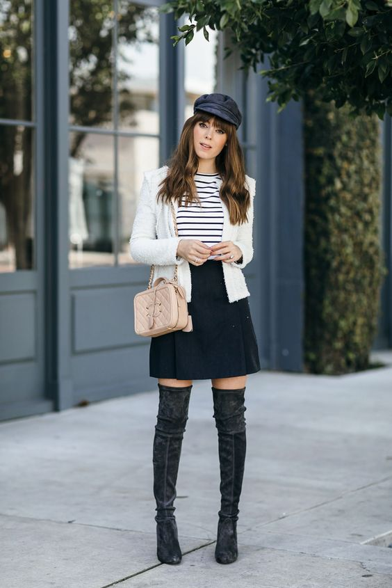 a black sude mini, a printed tee, a white jacket, tall black boots and a cap