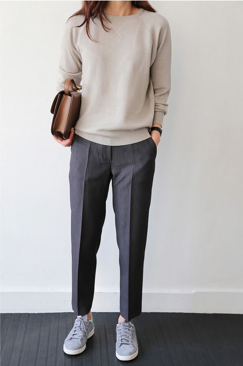 a work outfit with a neutral sweater, grey trousers, grey sneakers and a brown bag