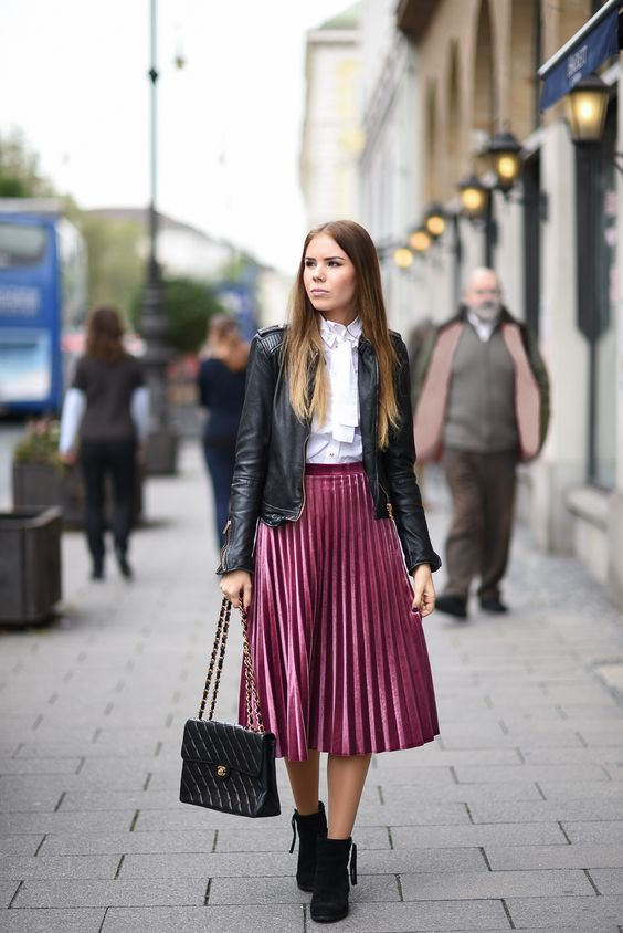 a white blouse, a black leather jacket, black suede booties, a dusty pink pleated midi and a black bag
