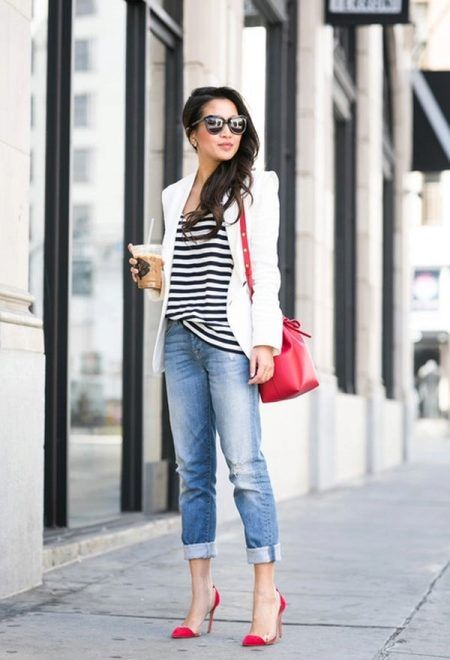 blue distressed cropped skinnies, a black and white top, a white blazer, red shoes and a bag