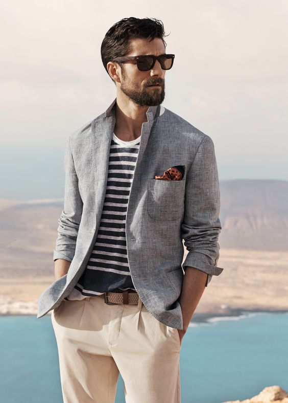 neutral pants, a striped t-shirt, a light blue jacket and sunglasses to go the seaside