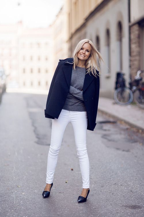 white jeans, black shoes, a grey sweater and a short black coat