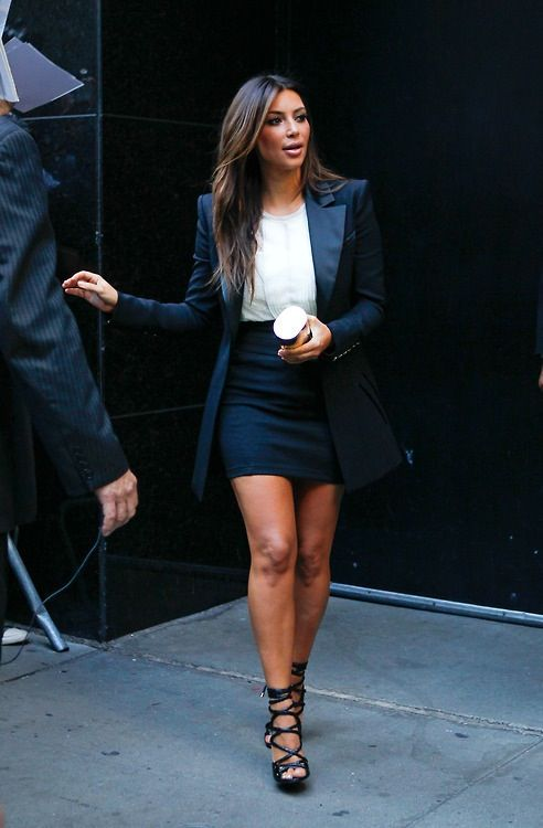 a black mini skirt, a white top, a black long blazer and black strappy heels