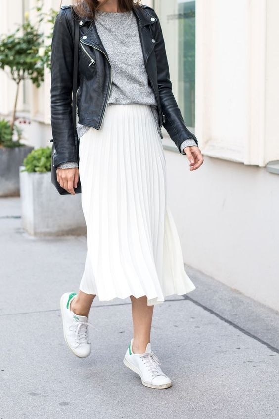 a grey long sleeve, a black leather jacket, a white pleated midi skirt, white sneakers
