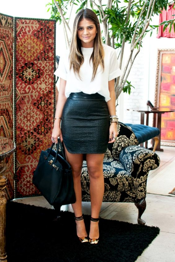 a light white top with short sleeves, a black shiny mini skirt, printed shoes with ankle straps