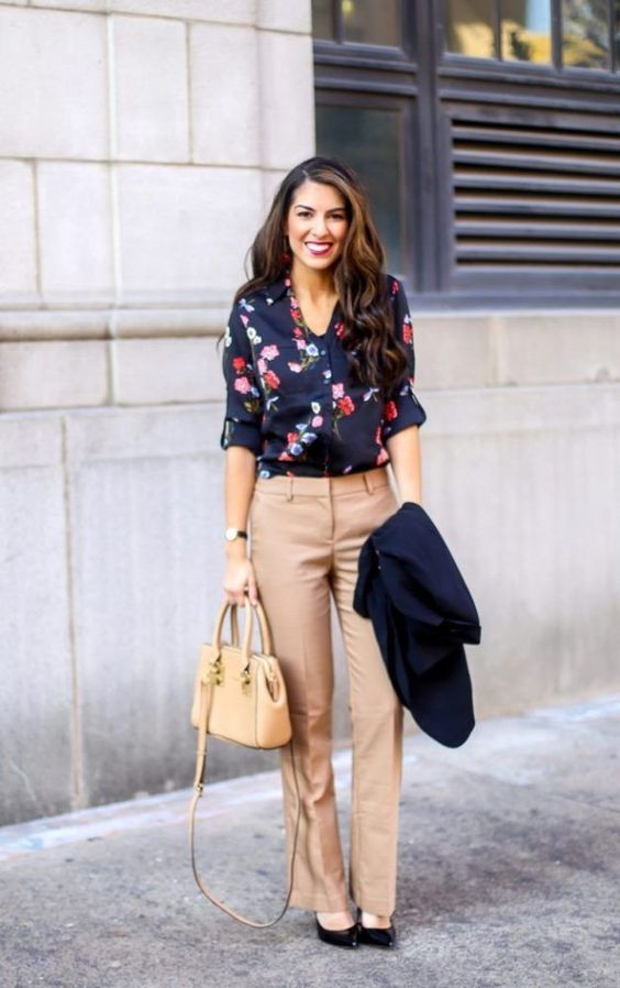 tan trousers, a navy floral blouse, a navy blazer, black heels and a small tan bag
