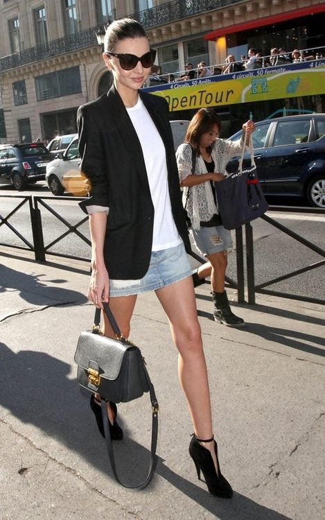 a long black blazer, a white tee, a denim mini skirt, black booties and a bag