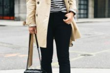 15 blue skinnies, a black and white striped top, black lacing up shoes, a neutral trench and a black bag