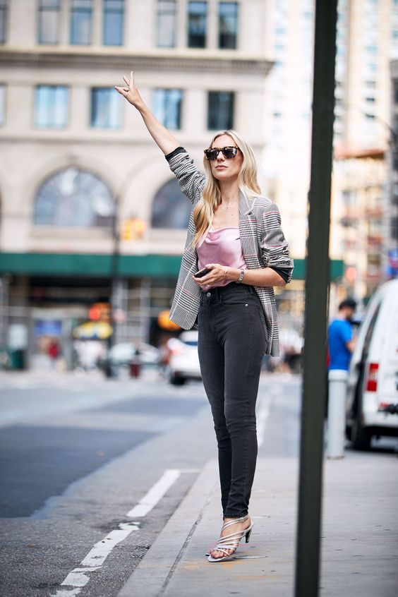 a checked jacket, a pink top, black skinnies and silver strappy shoes