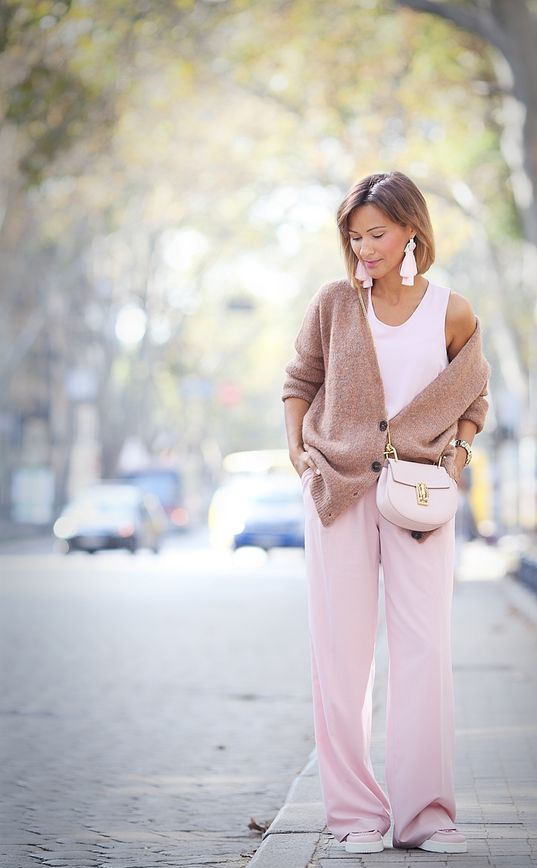 pink wide pants, a white top, a tan oversized cardigan, a bkush bag and tassel earrings