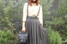 With beige shirt, black leather bag and brown suede boots