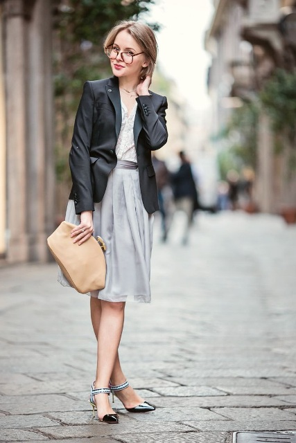 With black blazer, light gray dress and beige clutch