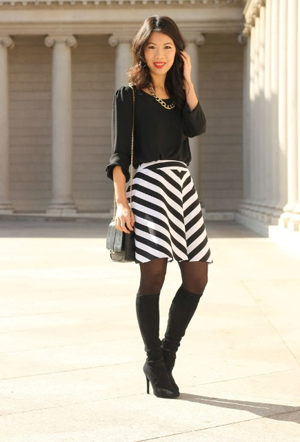 With black blouse, small bag and high boots