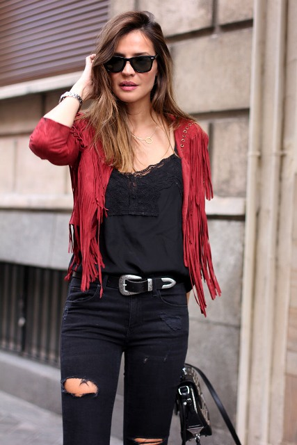 With black lace top, distressed pants and bag