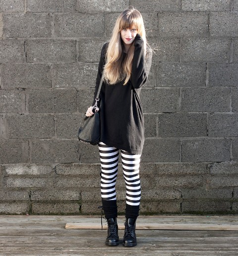 With black long sweater, mid calf boots and black bag