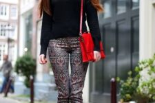 With black shirt, black ankle boots and red bag