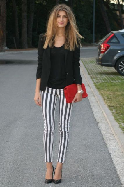 With black shirt, black blazer, red clutch and pumps
