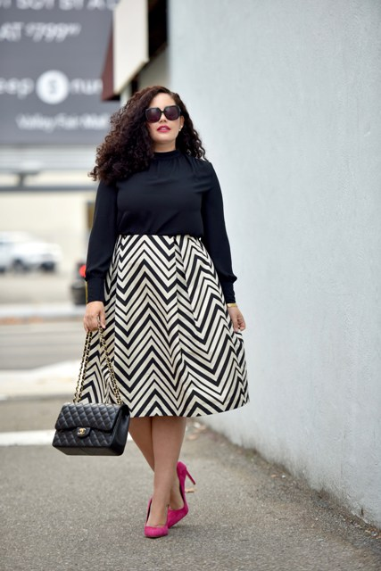 With black shirt, pink pumps and chain strap bag