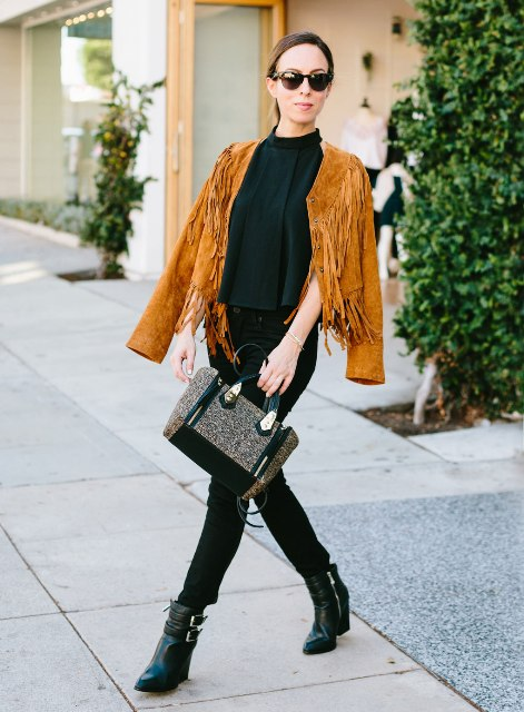 With black shirt, skinny pants, ankle boots and printed bag