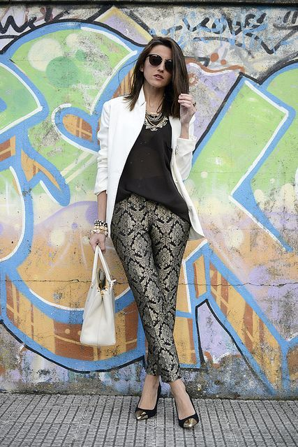 With black shirt, white blazer, pumps and white bag