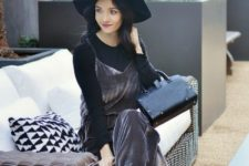 With black shirt, wide brim hat, black ankle boots and leather bag