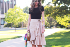 With black t-shirt, lace up sandals and unique bag