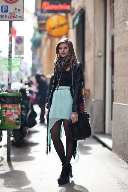 With black top, black leather jacket, ankle boots, printed scarf and bag