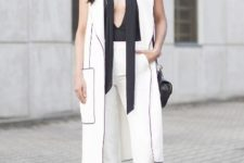 With black top, white long vest, black flat sandals and bag