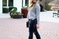 With distressed jeans, ankle boots and clutch