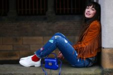 With funny jeans, white sneakers, red socks and blue bag