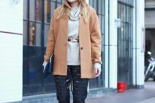 With gray sweater, white shoes, camel coat and clutch