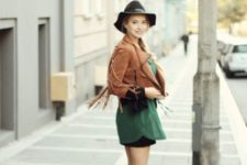 With green long blouse, black mini skirt, ankle boots and wide brim hat