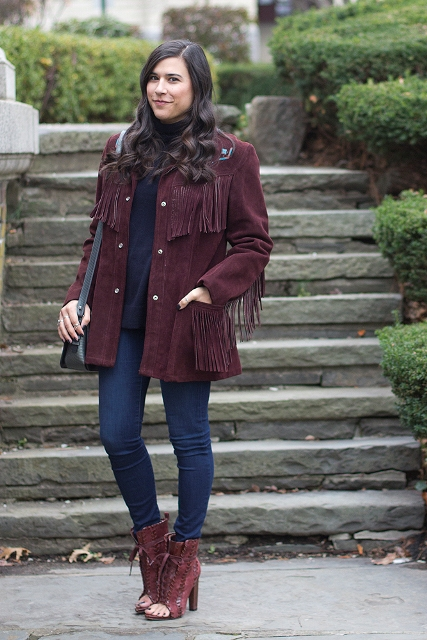 With navy blue turtleneck, skinny jeans, marsala cutout boots and black bag